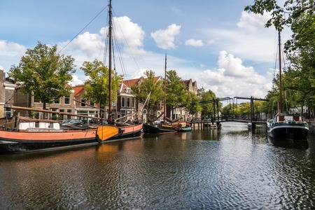 Traditional wooden sailing ships in water channel. Old historic harbor of Schiedam, The Netherlands