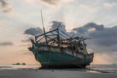The old wooden ruined fishing boat set aground on the beach at Sunset time Stock Photo