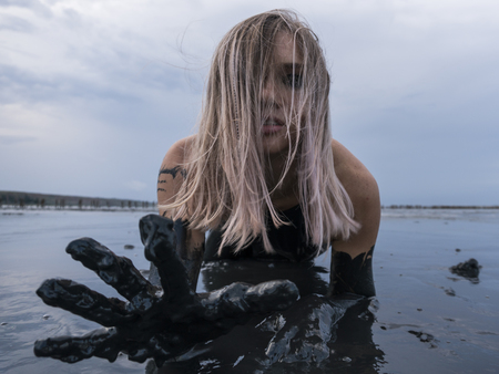 Stretched hand of Blonde Caucasian Girl Crawls Smeared in a Healthy Black Mud in old Firth