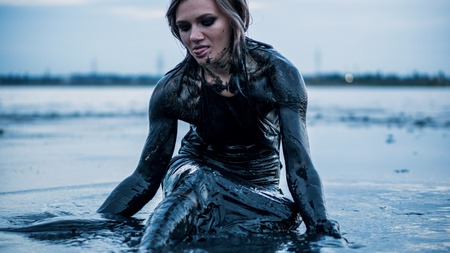 Portrait of Blonde Caucasian Girl Crawls Smeared in a Healthy Black Mud in old Firth