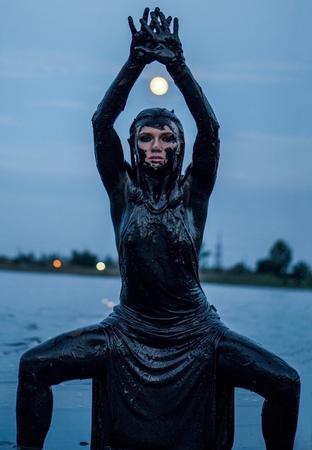 La ragazza caucasica snella rimane spalmata in un fango nero sano nel vecchio Firth. Le gambe divaricate e la luna sopra la sua testa