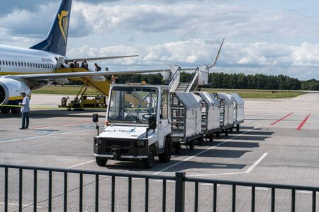 EINDHOVEN, THE NETHERLANDS - AUG 25, 2018: Ryanair aircraft on the runway. Ryanair is a major company for low cost flights. Baggage car