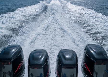 Vier Bootsmotoren hinterließen Schaum auf dem Wasser Standard-Bild