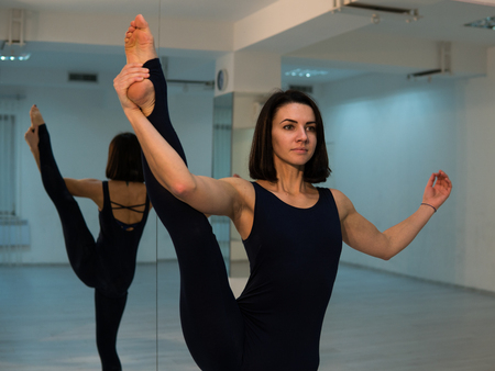 Young woman doing yoga pose and asana. Beautiful woman enjoying yoga indoors in sport clothes, working out in studio with mirrors