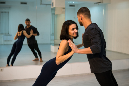 Young athletic couple in dark suits practicing pair yoga in studio with mirrors. Balancing in pair