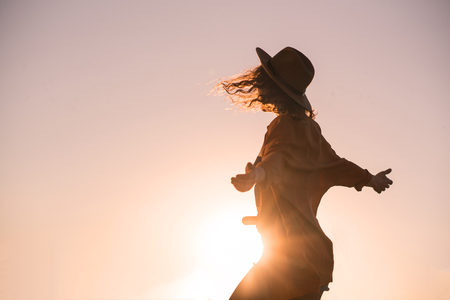 Curly chestnut-haired girl in jeans shorts and hat is spinning and have fun at sunset Banque d'images