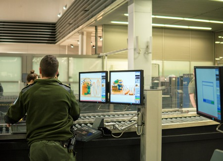 Airport security check point with Monitors and X ray scaner lent. Custom security worker checking baggage of visitors Standard-Bild