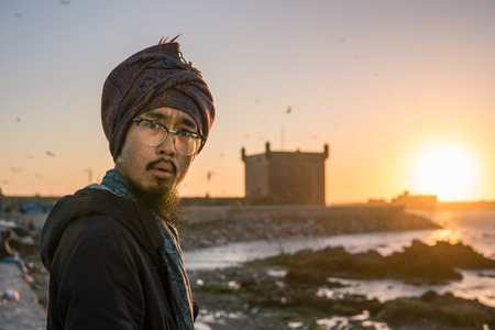 Young Asian Bearded Tourist man with Dreadlocks and scarf on head Having Fun in Essaouira, Morocco at the evening sunset time
