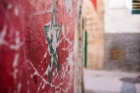Green star flag of Morocco on street wall in Essaouira Medina Foto de archivo