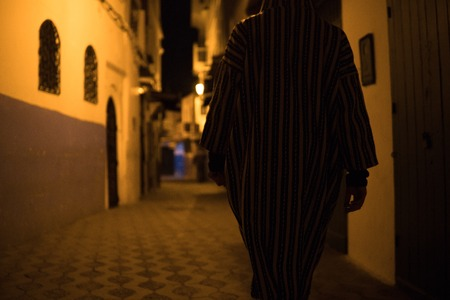 Man in Traditional moroccan djellaba walking on the street of Asilah Medina, on Atlantic Coast in Morocco