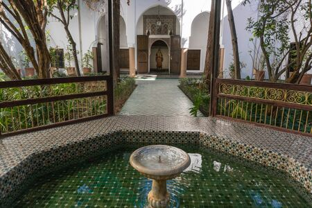 MARRAKESH, MOROCCO - JAN 20: Moroccan architecture traditional arabian design - Rich Riyad Dar Si Said mosaic interior. Beautiful Courtyard with fountain Редакционное