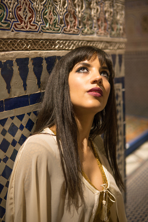 Beautiful Moroccan Girl in short golden dress and white mantle cloak in Rich interior of Picturesque Dar Si Said Riyad in Marrakech