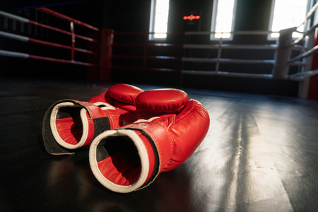 Pair of red boxing gloves in Boxing ring