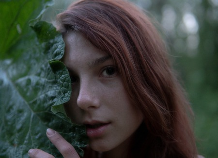 Close up portrait of Young woman with big Burdock leaf in the forest at Mysterious Twilight
