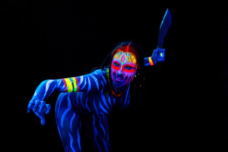 Portrait of Young naked bodyarted woman in blue glowing ultraviolet paint with big machete knife. Agressive avatar warrior woman amazon with pigtails hairstyle