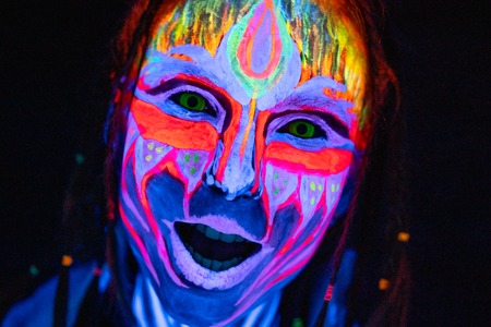 Close-up Portrait of Young bodyarted woman in blue glowing ultraviolet paint and Yellow eye lenses. Avatar entity amazon warrior girl with pigtails hairstyle