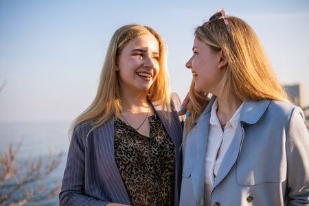 Two Twin teenage girls young woman laughing and having fun near the sea at sunset time