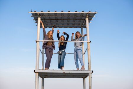 Three Young beautiful blonde girls in fashionable pantsuits are dancing on rescuer tower on the beach at evening Stock fotó