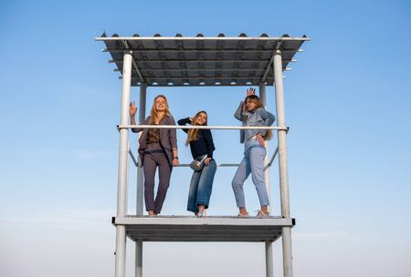 Trhree Young beautiful blonde girls in fashionable pantsuits are dancing on rescuer tower on the beach at evening