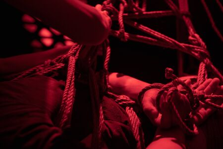 Female domination shibari performance in red erotic light. Bonded hanging man receive punishing and binding 写真素材