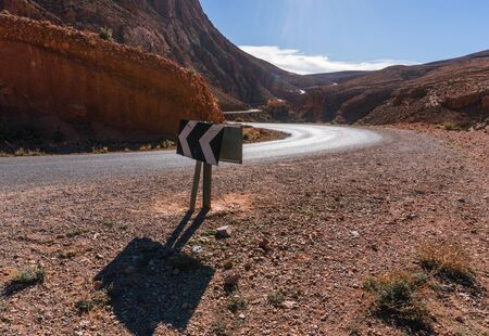 Arrow direction sign at Picturesque Serpentine mountain road in Gorges Dades in high Atlas, Morocco