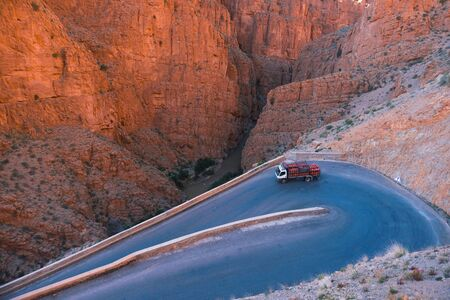 Truck with usual for north Africa red gasbags on Serpentine mountain road in Gorges Dades in high Atlas, Morocco