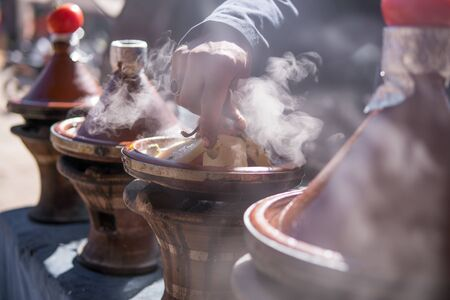 A hand of man cooking traditional Tajine in steam vapor on an outdoor barbecue at town square on the street in Morroco Stok Fotoğraf