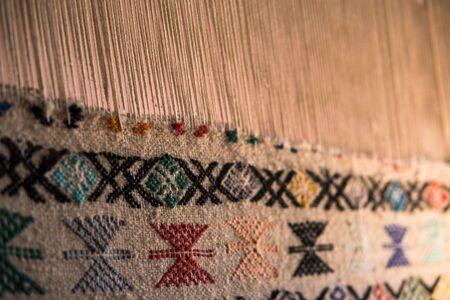 Werkzeug im alten Stil zum Weben eines Teppichs mit traditionellen Techniken auf einem Webstuhl, in der privaten Familienmanufaktur im Atlasgebirge in Tinghir, Marokko Standard-Bild