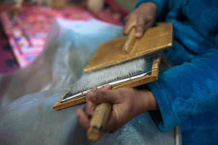Frau mit Bürsten, die eine Wolle zum Spinnen einer Wollschnur für marokkanische Berberteppiche vorbereiten