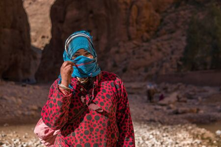 ATLAS MOUNTAINS, MOROCCO - 20 JAN: Nomad tribe people living in mountains near Tinghir or Tinerhir. Woman in canyon near the river. Todra gorge Редакционное