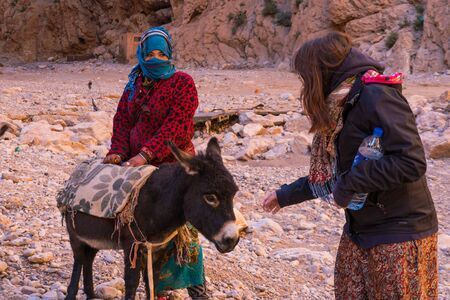 ATLAS MOUNTAINS, MOROCCO - 20 JAN: Tourist girl and Nomad tribe people living in mountains near Tinghir or Tinerhir. Woman with her daughters are herding donkeys in canyon near the river. Todra gorge
