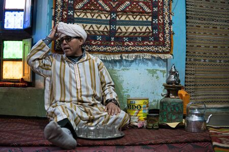Tinerghir, Morocco - January 2019 : Berber man invites visitors in his house where produce carpets for a glass of traditional mint tea with wormwood