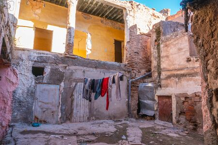 Pink Moroccan facade in City center. Window with drying hanging clothe. Ruins, Poor district. devastation. Lifestyle. In Marrakech the houses are traditionally pink. Morocco Stok Fotoğraf