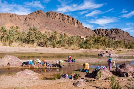 OURZAZATE, MOROCCO - JAN 2019: Berber women wash clothes in the river in beautiful picturesque place Oasis de Fint. Water day poor Moroccan tribes