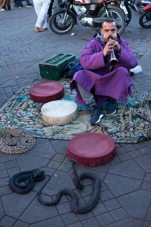 MARRAKESH, MOROCCO - 15 JAN 2019: Snake charmer at the Jemaa el-Fnaa square in Marrakesh, Morocco