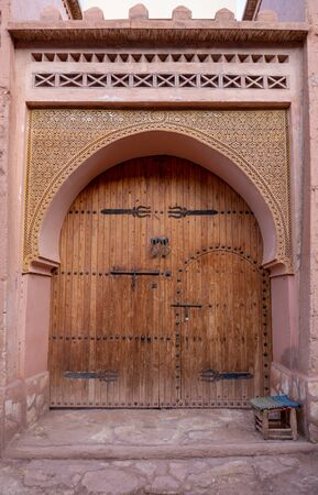 Traditional Moroccan style design of an ancient wooden entry door. In the old Medina in Ourzazate, Morocco. Typical, old, brown intricately carved, studded Stok Fotoğraf