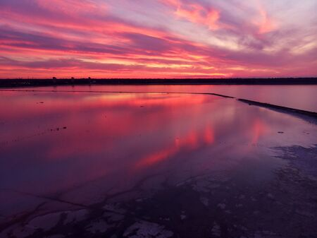 Aerial view of drone shot over water surface in twilight, golden hour sunset. Amazing view, firth surface reflecting majestic red and pink clouds Фото со стока