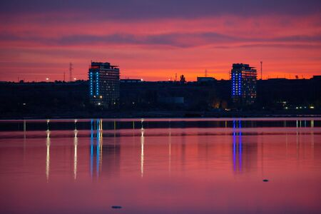 Beautiful twilight view of Kuyalnik liman with traffic and city light reflecting in calm water of firth with bright red clouds after sunset. Odessa, Ukraine. 写真素材