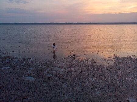Silhouette of a girl in the middle of lake at sunset. Beautiful girl posing alone in shallow water with light ripples