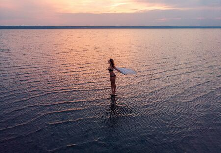Silhouette of a girl in the middle of lake at sunset. Beautiful girl posing alone in shallow water with light ripples Foto de archivo - 131362679