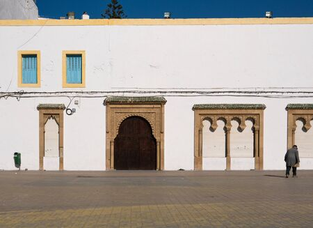 White building with traditional wooden arch door on the main square in Essaouira, Morocco