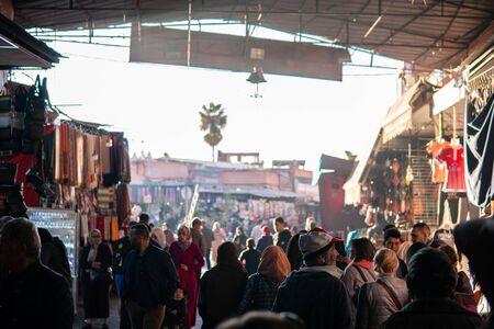 Marrakesh, Morocco - January 2019: Crowd of people strolling at souk bazaar big street market across the famous Jemaa el-Fnaa square