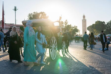 Marrakesh, Morocco - January 2019 : horse-drawn carriage cab waiting for passengers for tour in Jemaa el Fna square Редакционное