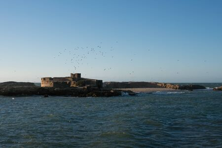Walled city of Essaouira in Morocco on sunset with white waves splashes on the rocks and shallow depth of field.