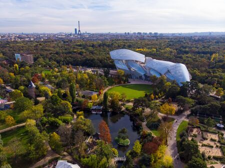 FRANCE, PARIS - OCT 2019: Aerial shot of Louis Vuitton Foundation museum modern building in Paris, France. Eiffel Tower on background, Boulogne forest around.