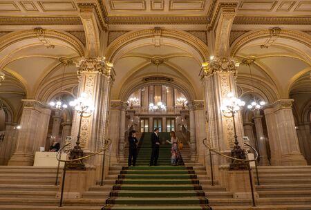 VIENNA, AUSTRIA - OCTOBER 2019: Conversation of tourist girl with opera theatre staff in Vienna State Opera House. Wiener Staatsoper stairs, fresco and rich gold interior