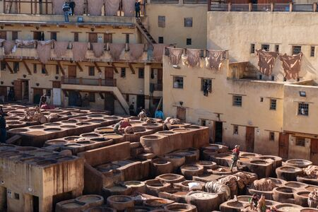 MOROCCO, FEX - January 2019: Workers in Chouara tannery in old medina in Fes, a traditional and old tannery with workers working making methods of leather