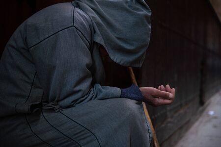 A poor beggar man in traditional Moroccan hoody djellaba outfit. fokiya, jellaba. Anonymous poor beggar in the street, Morocco