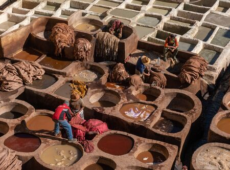 MOROCCO, FEX - January 2019: Man working in Chouara tannery in old medina in Fes, a traditional and old tannery with workers working making methods of leather