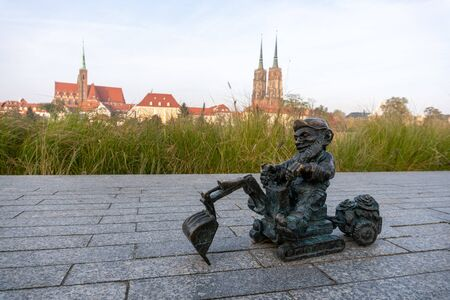 Bronze dwarf on the embarkment of Odra river with ostrow tumski on background. There are more than 600 dwarfs in Wroclaw.